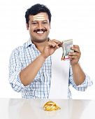 pic of indian money  - Portrait of a South Indian man counting money and smiling - JPG