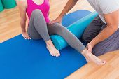 stock photo of personal assistant  - Trainer working with woman on exercise mat in fitness studio - JPG