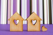 picture of two hearts  - Two wooden houses with hole in the form of heart with little heart on purple striped background - JPG