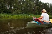 stock photo of canoe boat man  - Man fishing in river from canoe pure nature scene - JPG