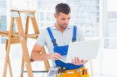 stock photo of step-ladder  - Repairman using laptop by step ladder in bright office - JPG