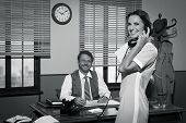 stock photo of 1950s  - Young 1950s secretary answering phone calls in director - JPG