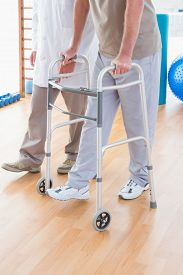 foto of zimmer frame  - Senior man on zimmer frame with therapist in fitness studio - JPG