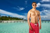 picture of jetties  - Man on beach with jetty at Maldives - JPG