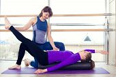 stock photo of personal trainer  - Aerobics Pilates personal trainer helping women group in a gym class - JPG