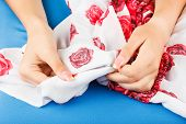 stock photo of tailoring  - Seamstress buttons zip hands - JPG