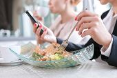 picture of lunch  - Close up photo of hands on a woman holding a fork eating a salad and a mobile phone reading some important emails, in a restaurant during business lunch selective focus