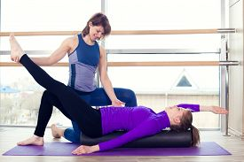 pic of pilates  - Aerobics Pilates personal trainer helping women group in a gym class - JPG