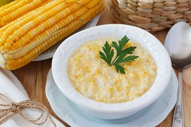 foto of brazilian food  - Brazilian corn soup canjiquinha in white vintage plate with fresh corn - JPG
