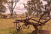 stock photo of horse plowing  - an old rusting horse drawn plow sits in the farm paddock - JPG