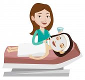 Cosmetologist applying cosmetic mask on face of client in beauty salon. Young woman lying on table i poster