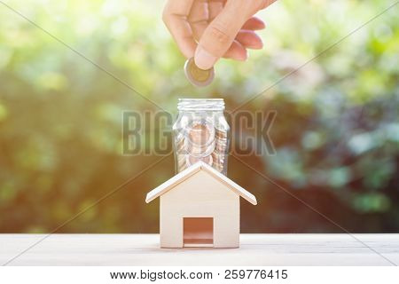 poster of Saving Money, Home Loan, Mortgage, A Property Investment For Future Concept : A Man Hand Putting Coi