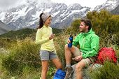 Camping lifestyle young people eating lunch outdoors hiking on New Zealand mountain trail track. Cou poster