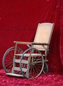 stock photo of antique wheelchair  - an antique wheelchair seen against red velvet - JPG