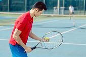 Side view of a determined Asian tennis player looking at the ball with concentration before serving  poster