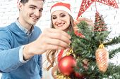 Son helping family decorating the Christmas tree with red and gold ornaments  poster