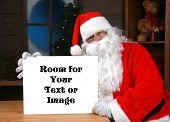 Постер, плакат: «Санта Клаус» проводит в пустой белый знак с «комната для вашего текста или изображения» во время в своей мастерской в