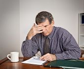 foto of mature men  - Tired stressed out businessman rubs his eyes while seated at a desk reading reports - JPG