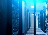 Shot Of Corridor In Big Data Dark Server Room With Bright Blue Equipment. Full Of Rack Servers And S poster