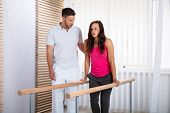 Therapists Assisting Female Patient In Walking With The Support Of Handrails poster