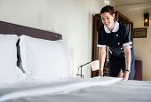 Housekeeper cleaning a hotel room poster