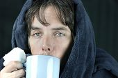 stock photo of housecoat  - Close-up of a sick man holding a tissue drinking from a hot mug.