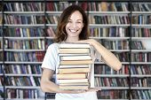 Woman Model College Student With Book At Library Holds Bunch Of Book, Looks Smart, Smiling To Camera poster