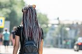 A Girl With Her Hair Braided In Braids Stands With Her Back. poster