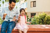 Image Of Happy Cute Little Girl Sitting With Dad On The City Street And Eating Ice-cream Outdoor. Fu poster