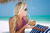 Beautiful blondy holding coconut in tropical beach at Agatti island
