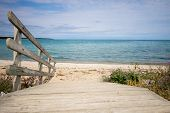 Path To The Beach. Wooden Ramp Leads To A Wide Sandy Beach With A Blue Water Horizon On A Sunny Sand poster