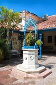Marble well with water in colonial style. Detail of yard from  home building in Santiago de Cuba, Cu