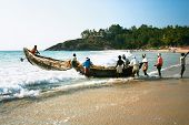 KOVALAM, INDIA - JANUARY 20 : Fishermen bring their traditional boat to the sea against waves Januar