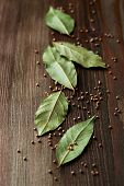 Bay leaves and mustard seeds on wooden background