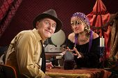image of seer  - Excited Caucasian man with grinning crystal ball reading lady - JPG