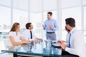 foto of half-dressed  - Smartly dressed young executives sitting around conference table in office - JPG