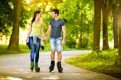 foto of roller-skating  - Young love couple spending free time  together - JPG
