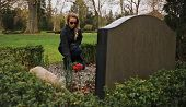 stock photo of grieving  - Young woman sitting at the gravestone of her family member - JPG