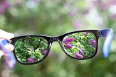 image of ophthalmology  - eyeglasses in the hand over blurred background - JPG