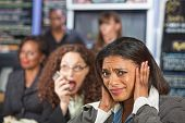 picture of disrespect  - Bothered business person covering ears while person talks - JPG