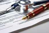 image of statements  - Stethoscope on medical billing statement on table - JPG