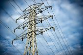 picture of hydro  - Looking up at a towering electric hydro transmission tower standing against a cloudy blue sky - JPG