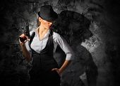 picture of gangster  - Woman with gun on grey wall background - JPG