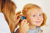 pic of ear  - This is a photograph of Pediatrician doctor examining little girl - JPG