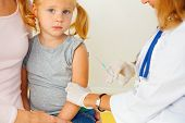 stock photo of redhead  - This is photograph of Doctor vaccinating small redhead girl - JPG