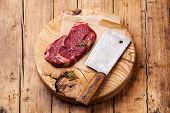 picture of ribeye steak  - Raw fresh meat Ribeye Steak and meat cleaver on wooden background - JPG