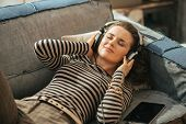 stock photo of couch  - Young woman laying on couch and listening music listening music in headphones - JPG
