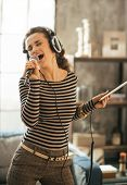 stock photo of singing  - Young woman singing karaoke in loft apartment - JPG