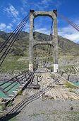 image of suspension  - Old abandoned suspension bridge over the river Katun Altai Russia - JPG