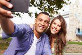 image of two women taking cell phone  - Couple Taking Selfie By Tower Bridge In London - JPG